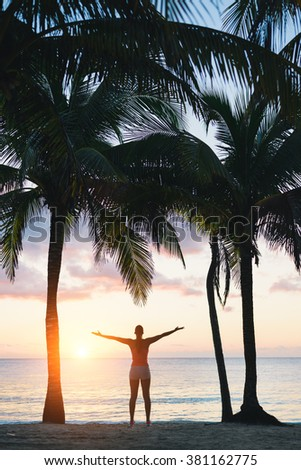 Blissful fitness woman enjoying outdoor summer relaxing sunrise or sunset at the beach after workout. Happy female athlete exercising during vacation under tropical palms at Riviera Maya, Mexico. - stock photo