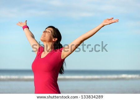 Blissful fitness woman raising arms to the sky on beach at sunset after working out. Happy female athlete feeling the breeze on sea background. Achievements and goals on sport concept. - stock photo