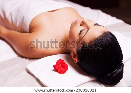 Blissful moments. Top view of beautiful young woman wrapped in towel lying on massage table and keeping eyes close - stock photo