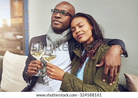 Blissful romantic young African couple relaxing in each others arms while enjoying a drink of white wine at a restaurant table - stock photo