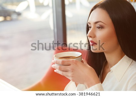 Blissful warmth. Top view closeup shot of a young attractive businesswoman enjoying her warm drink at the local cafe - stock photo