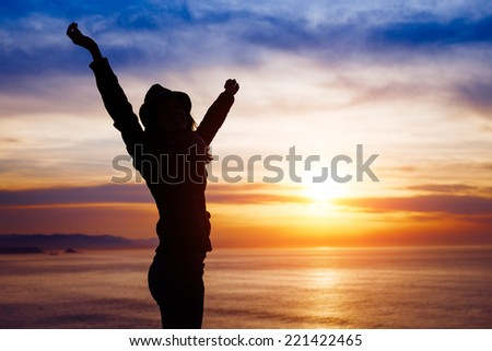 Blissful woman enjoying freedom and happiness on beautiful sunset towards the ocean and sky. - stock photo