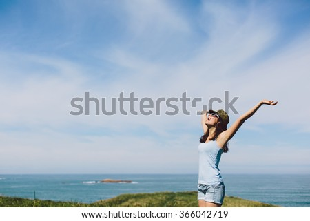 Blissful woman enjoying freedom raising arms to the sky towards the sea. Girl having fun and celebrating life  on coast vacation . - stock photo