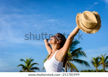 Blissful woman on tropical caribbean vacation raising arms to the sky. Freedom and travel concept. Brunette woman enjoying summer holidays. - stock photo