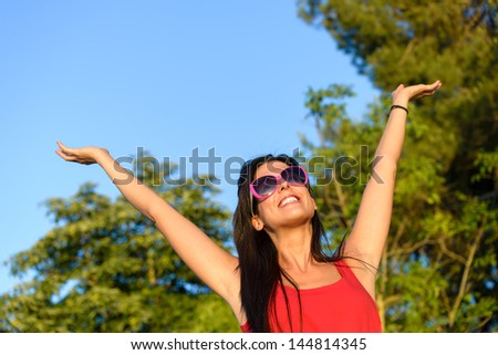 Blissful woman raising arms to the sky in forest surrounded by trees. Carefree, happiness, hope and vitality concept. Caucasian girl relaxing and enjoying life on summer nature outdoors. - stock photo
