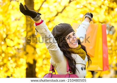 Blissful woman raising shopping bags  and arms while having fun buying in autumn. Successful female shopper outside in fall season. - stock photo