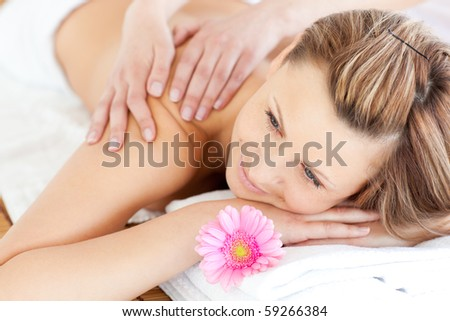 Blissful young woman enjoying a back massage in a spa center - stock photo