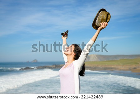 Blissful young woman with arms up towards the sea enjoying freedom, tranquility and relax. Beautiful happy female on coast travel feeling the ocean breeze. - stock photo