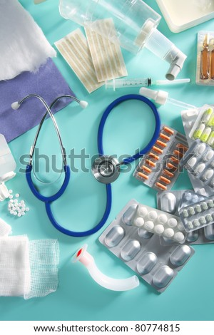 blister of medical pills and pharmaceutical stuff with stethoscope over green background - stock photo