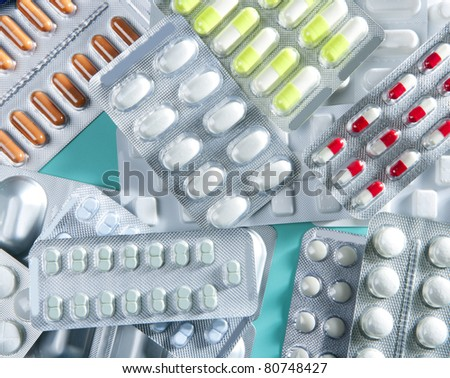 blisters of medical pills over green background as a pharmaceutical industry concept - stock photo