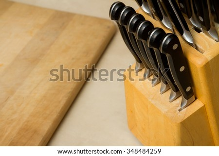 Block holding a bunch of knives with a cutting board on teh counter