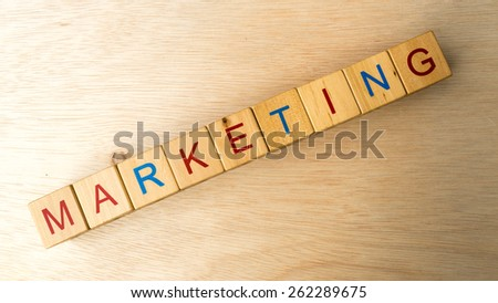 Block of alphabet letters forming the word MARKETING on wooden surface. Concept of common marketing business terms. Slightly defocused and close-up shot. Copy space.