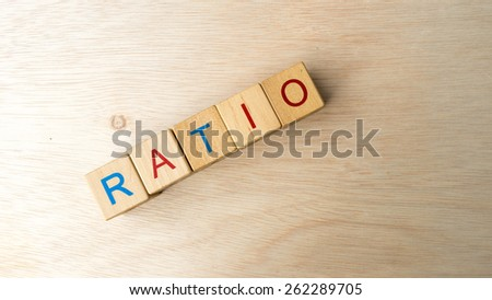 Block of alphabet letters forming the word RATIO on wooden surface. Concept of common marketing business terms. Slightly defocused and close-up shot. Copy space.