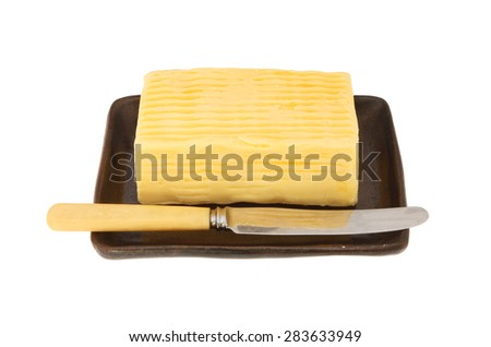 Block of butter and butter knife on a dish isolated against white - stock photo