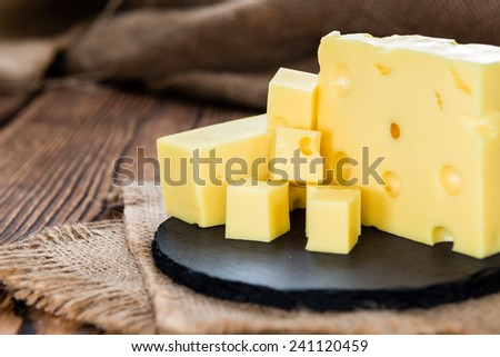 Block of Cheese (close-up shot) on vintage wooden background - stock photo