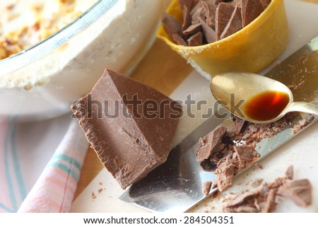 Block of chocolate, some chopped in measuring cup, with vanilla, and mixing bowl of batter - stock photo