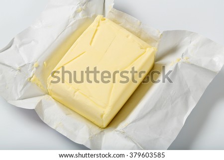 block of fresh butter on white background - close up - stock photo
