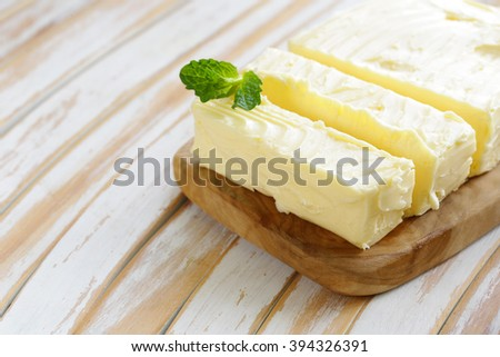 block of fresh organic butter on a wooden board