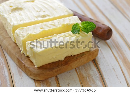 block of fresh organic butter on a wooden board - stock photo