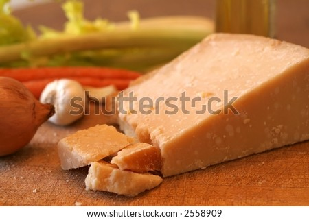 Block of parmesan cheese and fresh vegetables on cutting board (natural lighting) - stock photo