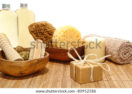 Block style bar aromatherapy organic soap and natural body care accessories with sponges and soft towel in earthy colors over white for a pampering holistic bath hygiene treatment in a spa - stock photo
