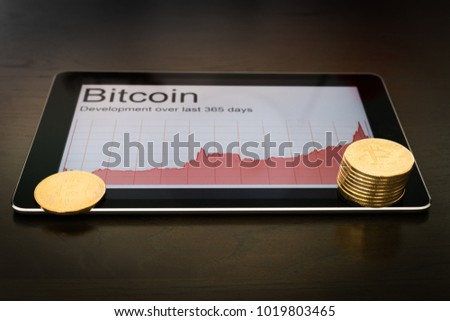 Blockchain concept : Rise of Bitcoin price. Digital tablet showing increasing price graph with coins of the cryptocurrency.