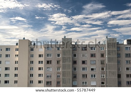 blocks of flats against blue cloudy sky - stock photo