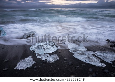 Blocks of ice from the glaciers break up and is washed ashore by the strong waves of the sea in Iceland. - stock photo