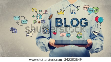 Blog concept with young man holding a tablet computer  - stock photo