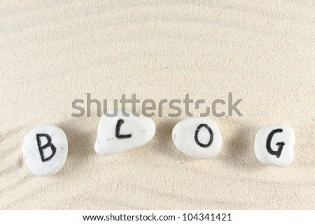 Blog word on group of stones with sand background