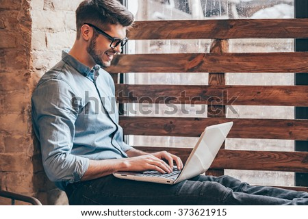 Blogger at work.Side view of handsome young man working on laptop and smiling while sitting at windowsill  - stock photo