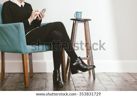 blogger girl checking her smartphone while drinking a coffee