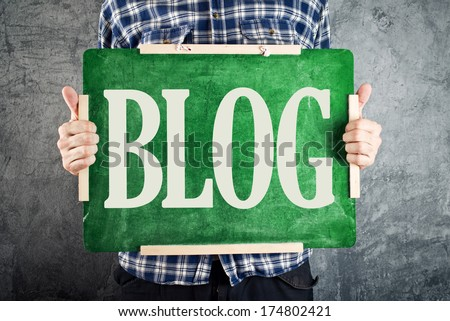 Blogger. Man holding chalkboard with word Blog written on. - stock photo