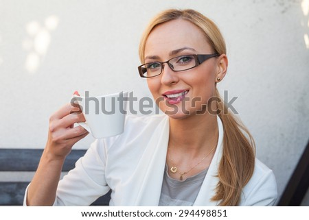 Blon hair girl in glasses and suit  sitting on the bench with cup of coffee in her hands