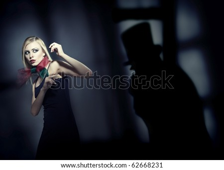 Blond afraid lady in the dark interior with deep shadows. Artistic colors and grain added - stock photo