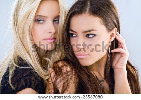 blond and brunette portrait, studio shot - stock photo
