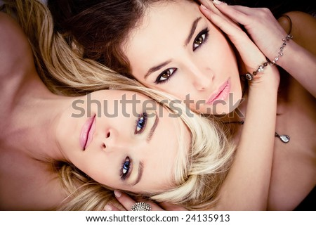 blond and brunette women portrait, lying down - stock photo