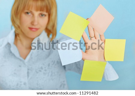 blond attractive businesswoman showing her hand with office notepads