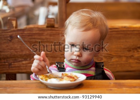 Blond babe eats pancakes at a wooden table in a cafe - stock photo