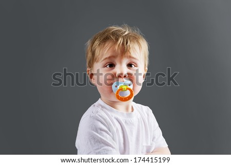 Blond baby boy or toddler with pacifier - stock photo