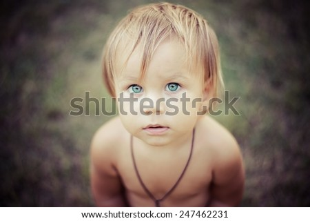 Blond baby boy with big blue eyes outdoors in summer. - stock photo