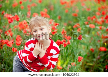 Blond baby girl in field of poppies. - stock photo