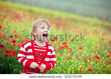 Blond baby girl in field of poppies. She looks surprised. - stock photo