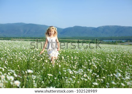 Blond baby girl in wreath running in field of camomiles - stock photo