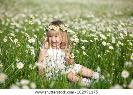 Blond baby girl in wreath sitting in field of chamomiles