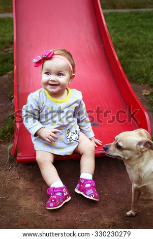 blond baby girl with chihuahua dog outdoor autumn portrait - stock photo