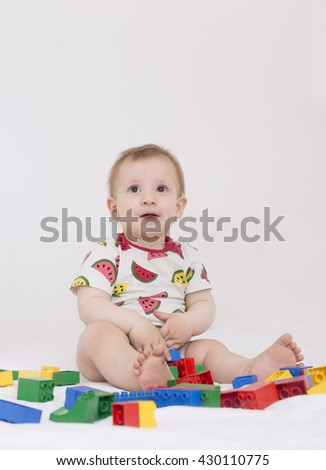 blond baby toddler with dark eyes sitting and playing with multicolored plastic construction kit indoors - stock photo