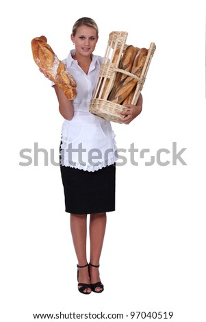 Blond bakery worker holding bread - stock photo