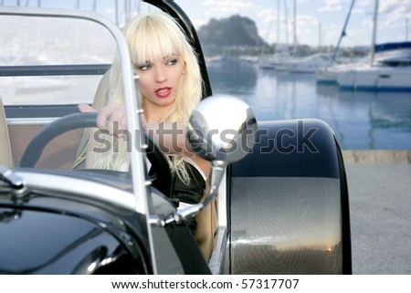 blond beautiful black driving sport car on blue mediterranean marina young sexy girl [Photo Illustration] - stock photo