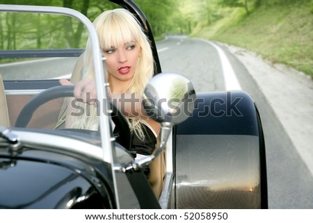 blond beautiful black sport car driving on forest road young sexy girl [Photo Illustration] - stock photo